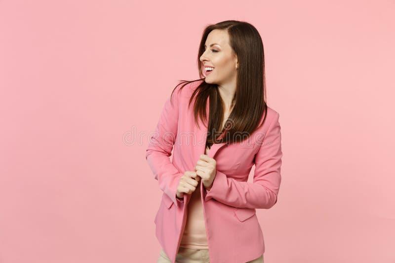 握在夹克的可爱的微笑的年轻女人画象手看在旁边在粉红彩笔墙壁背景 库存照片