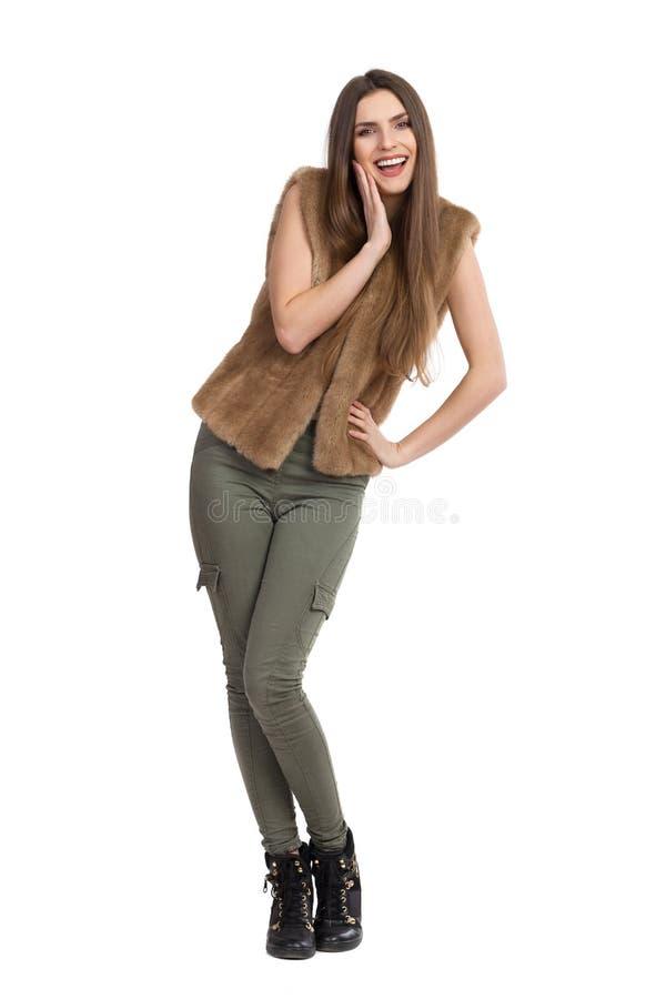 握在奇恩角的毛皮背心的微笑的妇女手 免版税库存图片