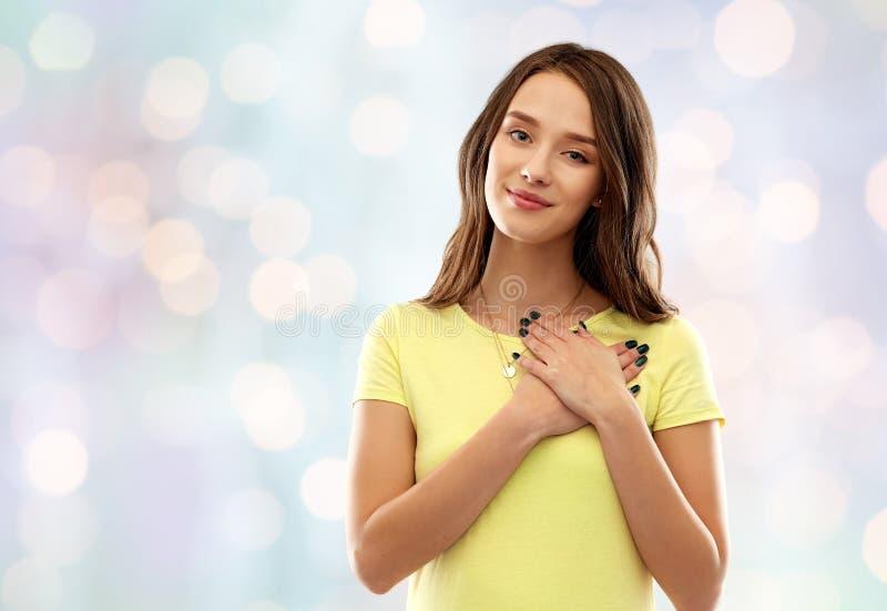 握在心脏的微笑的十几岁的女孩手 库存图片