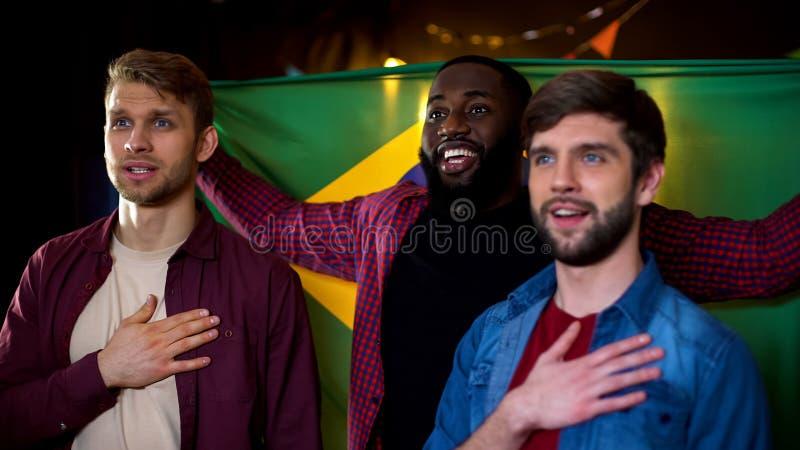 握在心脏的快乐的巴西爱好者手,听专题歌,体育 库存照片