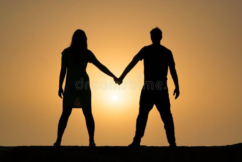 握在日落的夫妇的剪影手 免版税库存图片