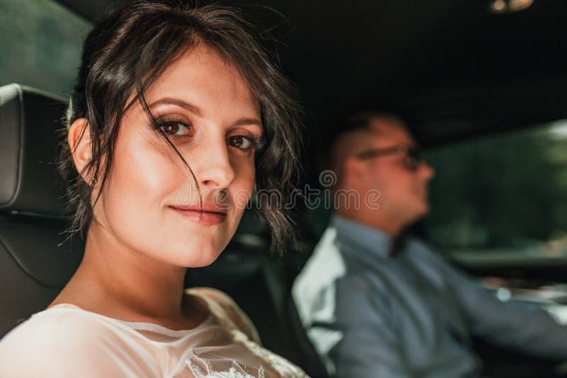 握在时髦的黑汽车的豪华典雅的婚姻的夫妇手 华美的新娘和英俊的新郎减速火箭的样式的 免版税图库摄影