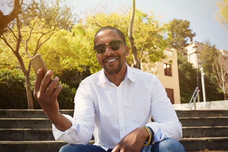 握在智能手机的年轻可爱的非洲人手,当坐在晴朗的城市公园时 愉快的事务的概念 图库摄影
