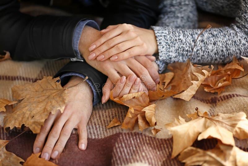 握在格子花呢披肩的爱的年轻夫妇手在秋天公园 免版税库存图片