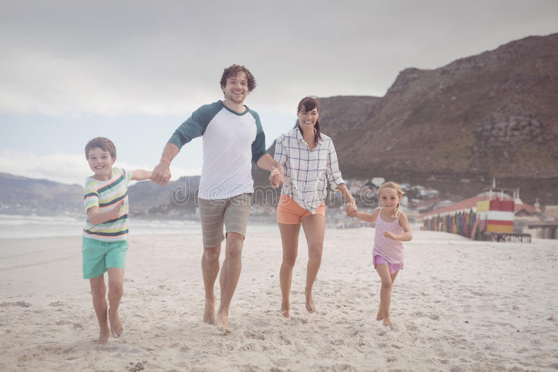 握在沙子的家庭画象手在海滩 免版税库存照片