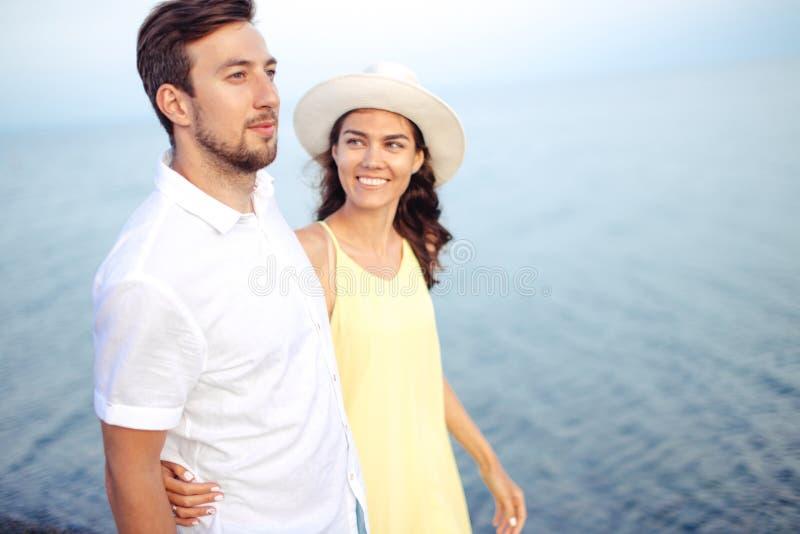 握在海滩和步行的夫妇手和一起享用 免版税库存图片