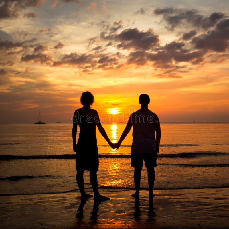 握在海滩的新夫妇现有量在日落 免版税图库摄影