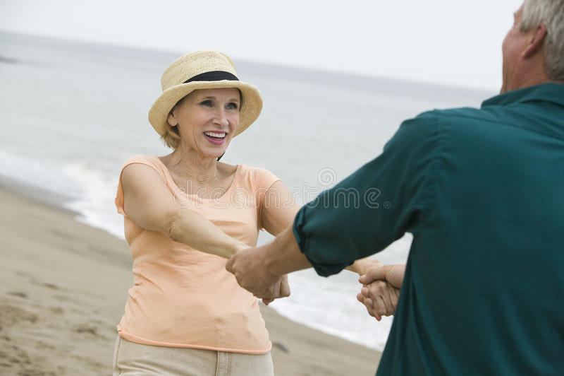 握在海滩的成熟夫妇手 免版税图库摄影