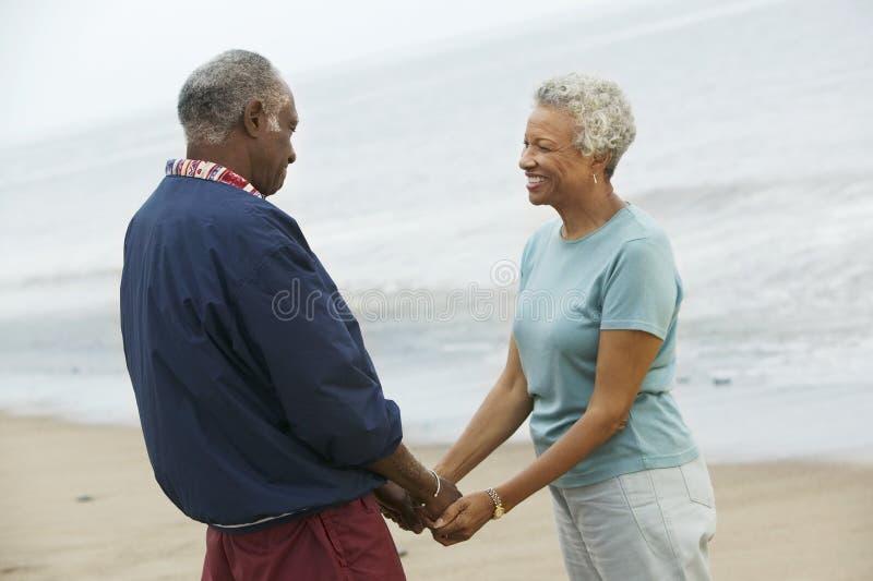 握在海滩的资深夫妇手 库存照片