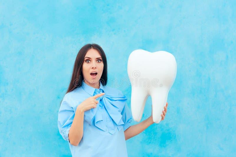 握在牙医概念图象的滑稽的妇女过大的牙 免版税库存照片