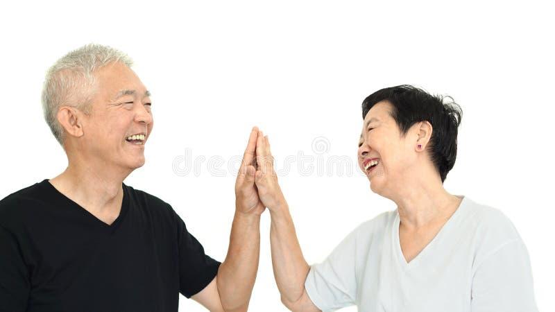 握在白色孤立backgro的愉快的亚洲资深夫妇手 库存图片