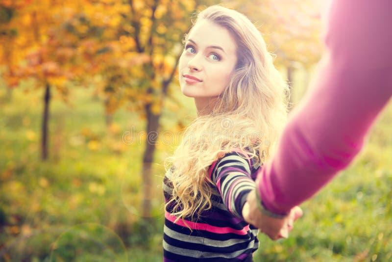 握在秋天背景的少妇手 库存照片