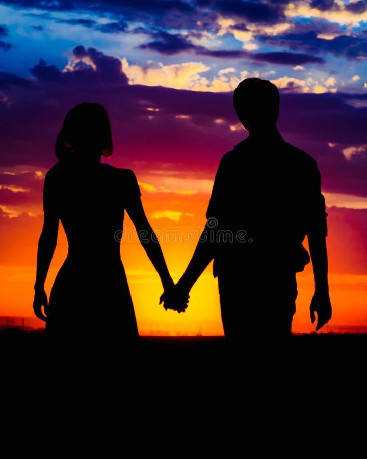 握在美丽的太阳的背景的男人和妇女手 免版税图库摄影