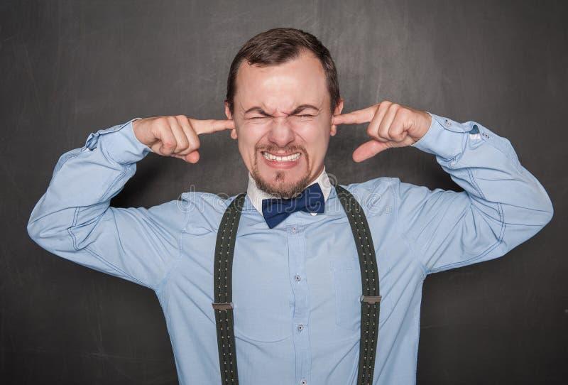 握在耳朵的不快乐的老师人手指 免版税库存图片