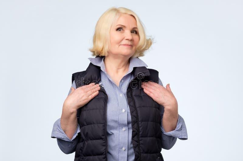 握在胸口感觉的白肤金发的老妇人手被接触或喜欢 库存图片