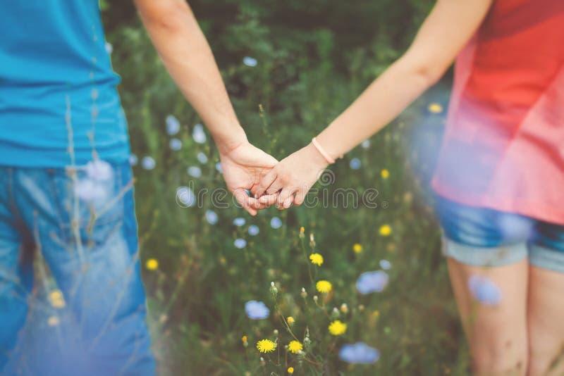 握在花田的青少年的夫妇手 免版税库存图片