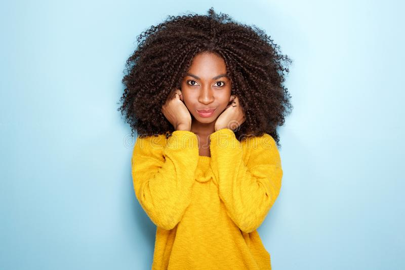 握在蓝色背景的美丽的年轻非洲妇女耳朵 免版税库存照片