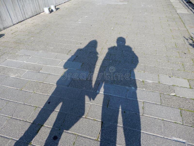 握在街道上的夫妇、男人和妇女的阴影手 免版税库存照片