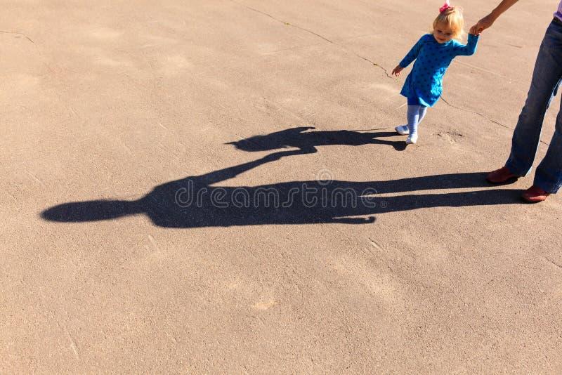 握在路的母亲和女儿的阴影手 库存照片