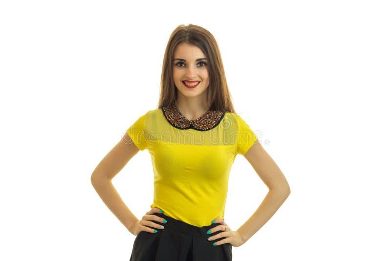 握在边和面孔的一个迷人的年轻微笑的女孩手在明亮的女衬衫的照相机 免版税图库摄影
