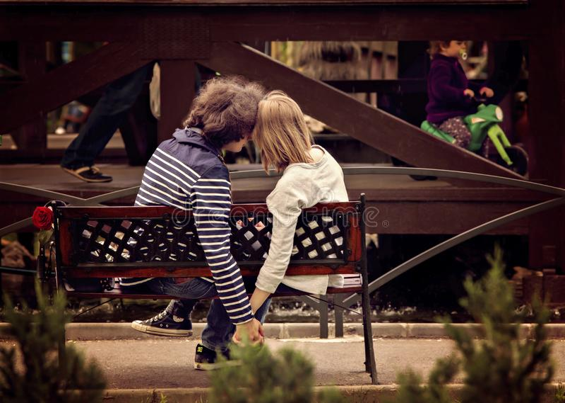 握在长凳的年轻夫妇手在公园 免版税库存照片