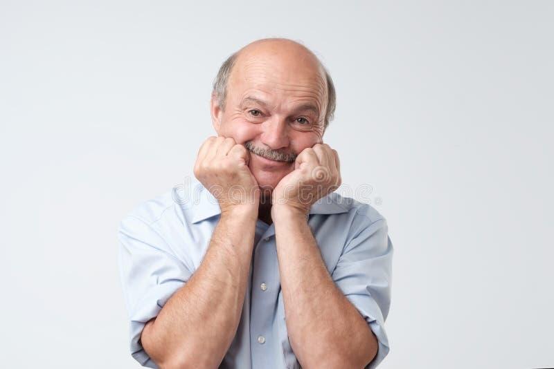 握在面颊的手,微笑和扫视照相机的逗人喜爱的秃头白种人男性画象  免版税库存图片