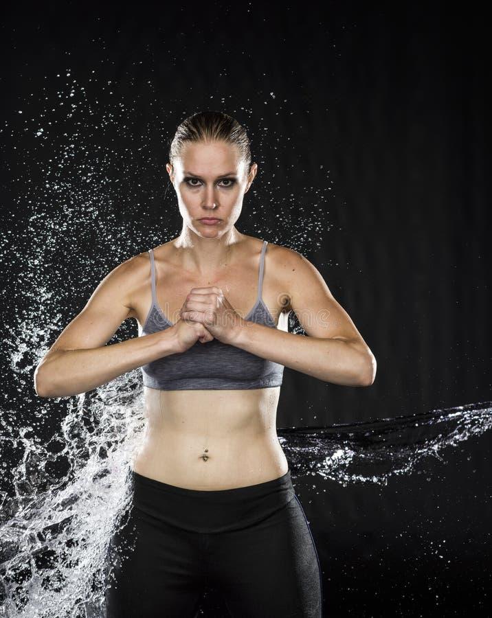 握在水飞溅的运动妇女拳头 库存照片