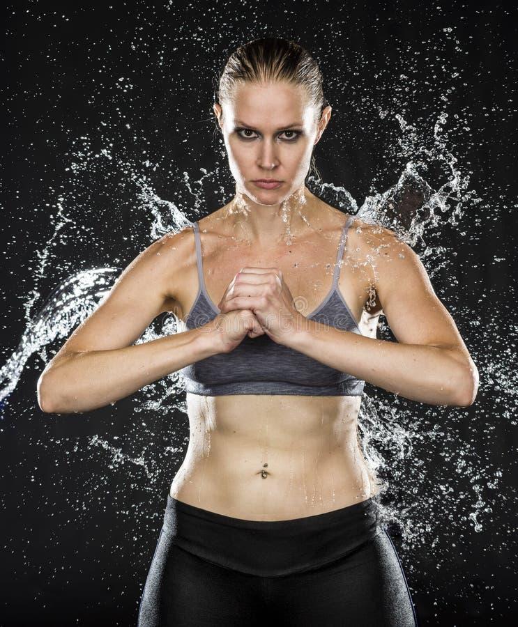 握在水飞溅的运动妇女拳头 库存图片