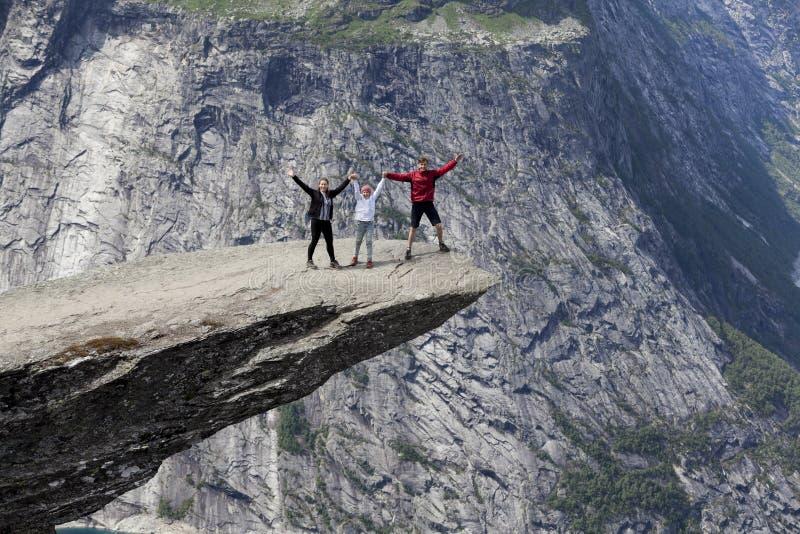 握在Trolltunga岩层的三人家庭手 突出的峭壁在奥达,霍达兰县,挪威 库存照片