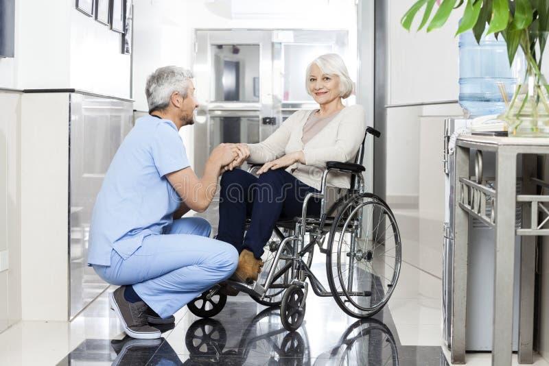握在Wheelchai的生理治疗师微笑的资深妇女的手 免版税图库摄影