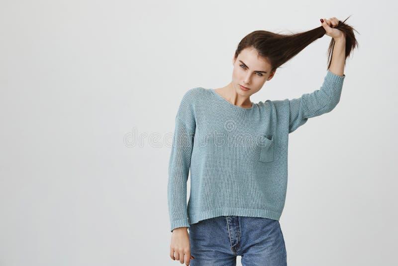 握头发顶上用手和凝视与挥动的神色的照相机的可爱和肉欲的欧洲妇女 免版税库存图片
