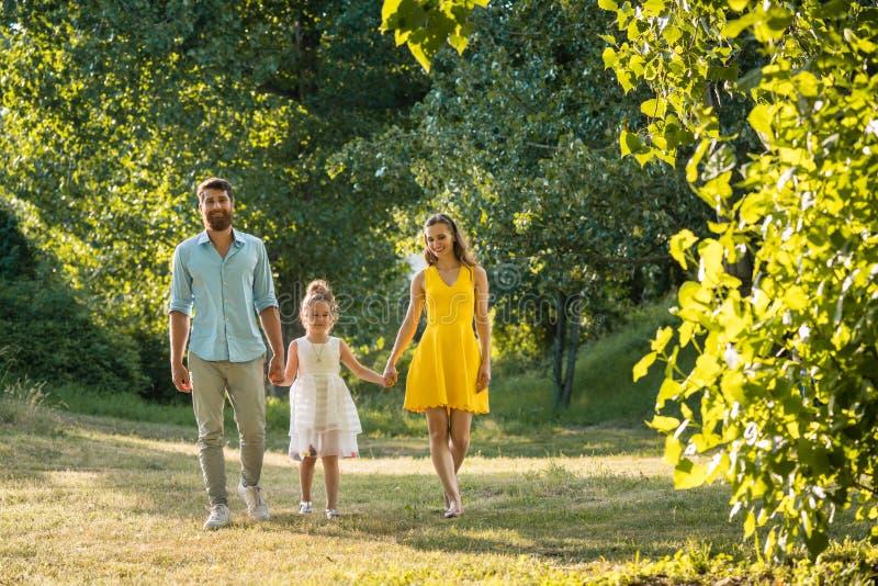 握女儿的手的充满爱心的父母,当一起时走 图库摄影