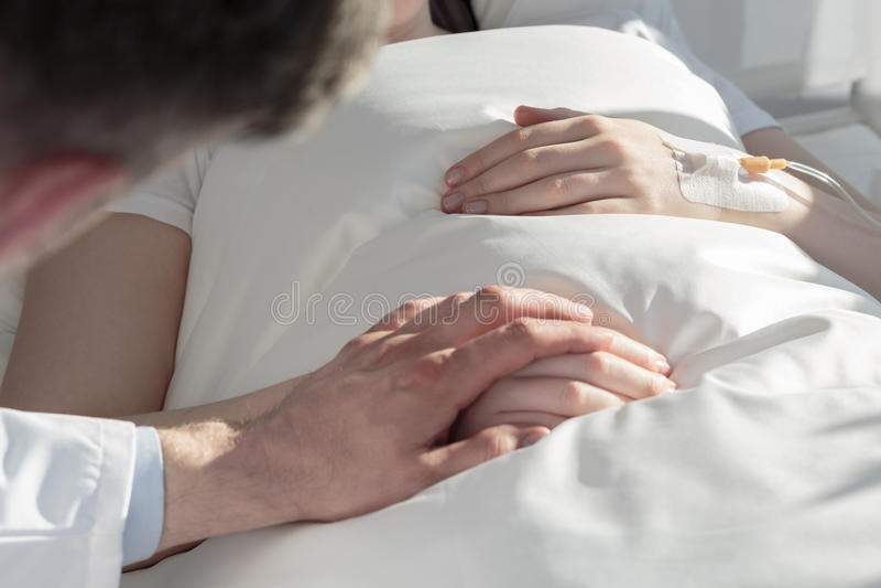 握女孩的手的癌症医师 免版税库存照片