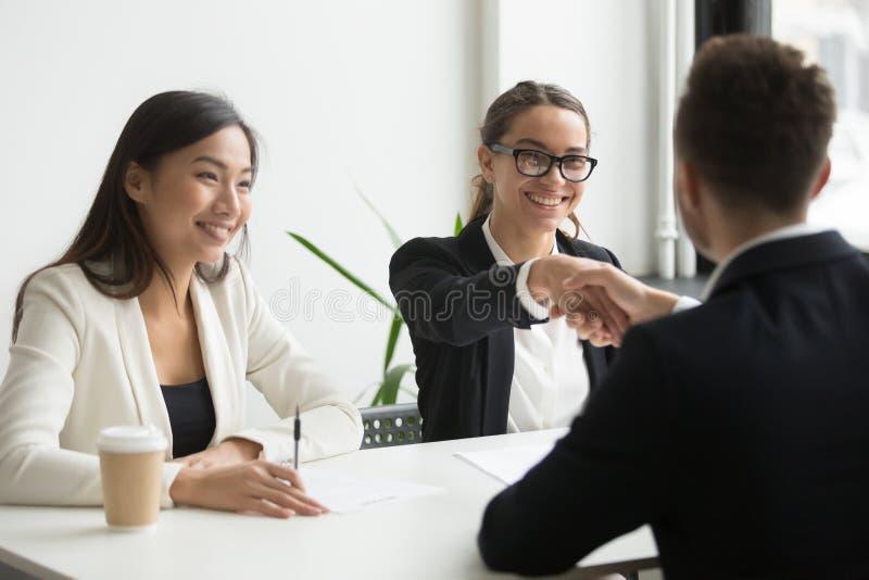 握女性工友的手的商人在公司meeti期间 免版税库存照片