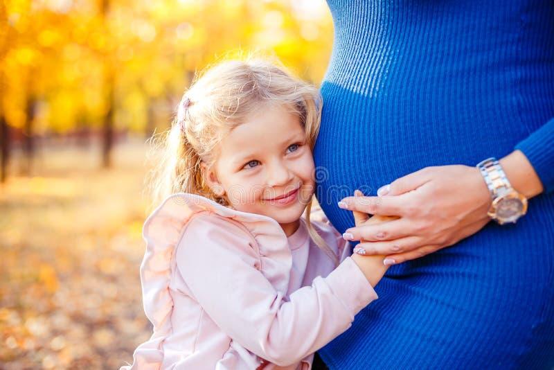 握她怀孕的母亲的腹部的美丽的女孩画象 免版税库存照片