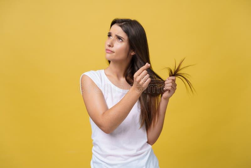 握她有看的妇女手护发问题的损坏的头发分叉长的头发 免版税库存图片