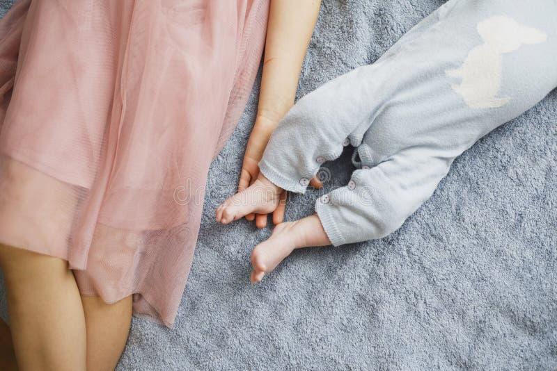 握她的兄弟脚的女孩 新出生的男婴 逗人喜爱的小的腿 免版税图库摄影