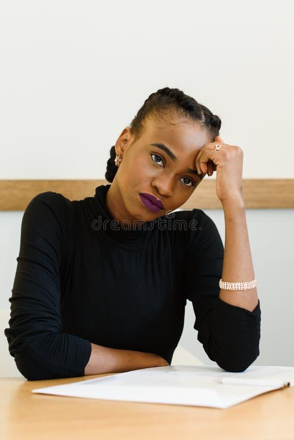 握她的前额用手的哀伤的担心的非洲或黑人美国妇女在书桌 免版税库存照片