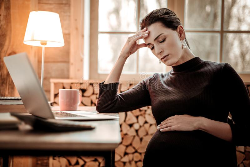 握她的前额的哀伤的了无欢乐的孕妇 免版税库存照片