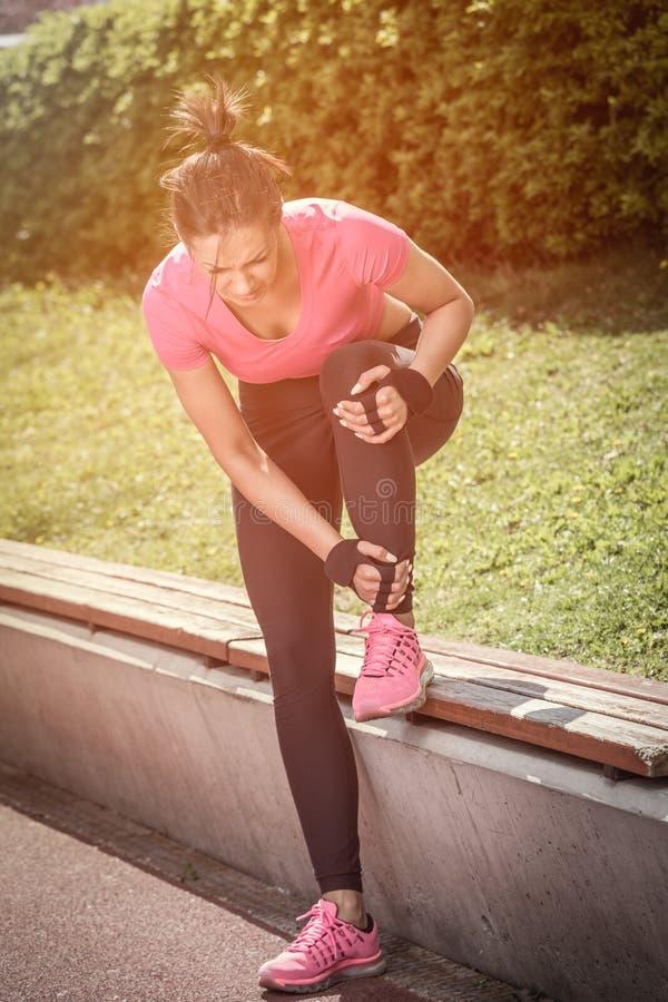 握她的受伤的腿的母赛跑者在连续轨道旁边 免版税库存照片