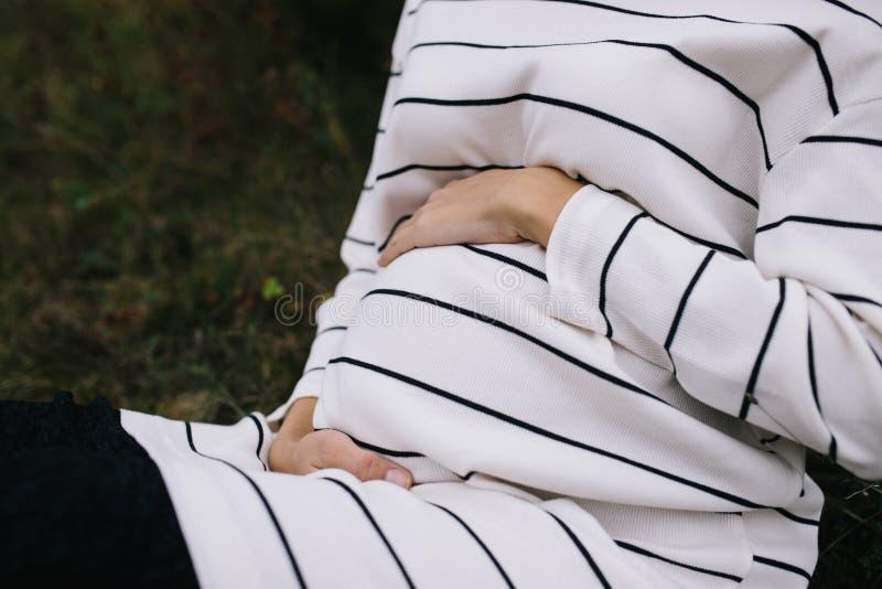 握她的在她圆鼓的腹部的孕妇特写镜头手 图库摄影