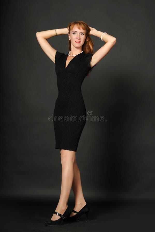 握她的头发的一件黑礼服的一名妇女 免版税库存照片