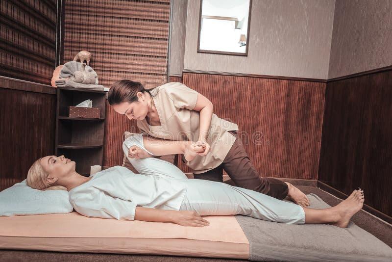 握她的客户腿的好泰国妇女 免版税库存照片