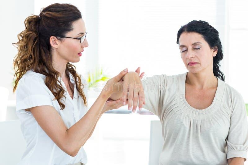 握她的患者胳膊的治疗师 库存照片
