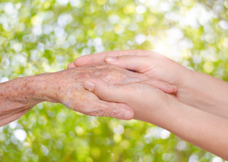 握她的祖母手的少妇 免版税图库摄影