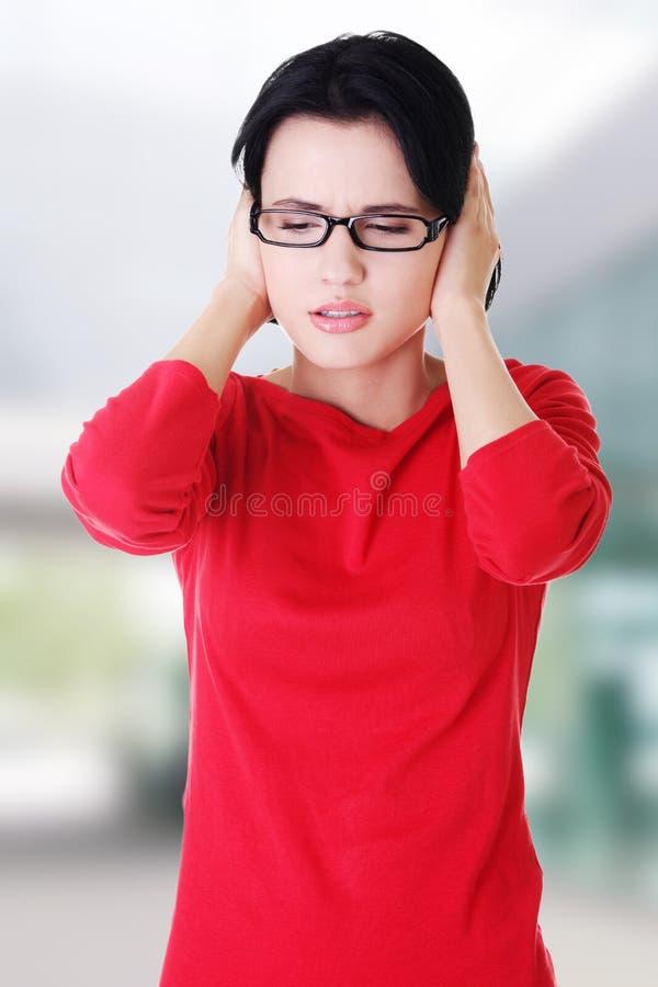 握她的耳朵的沮丧的少妇 图库摄影