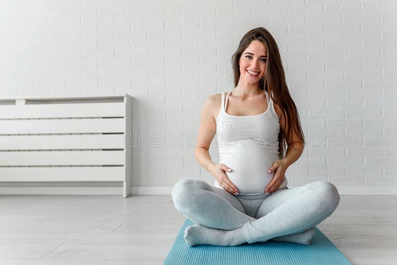 握她的腹部的怀孕的体育妇女 图库摄影
