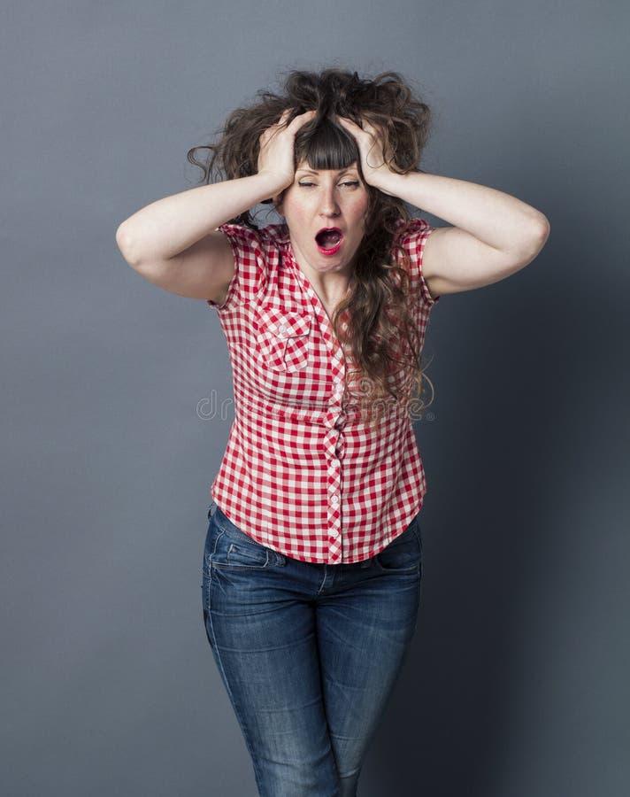 握她的顶头和长的头发的乏味深色的妇女,打呵欠 免版税库存照片