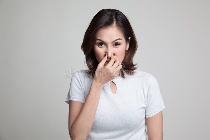 握她的鼻子的年轻亚裔妇女由于难闻的气味 免版税库存照片