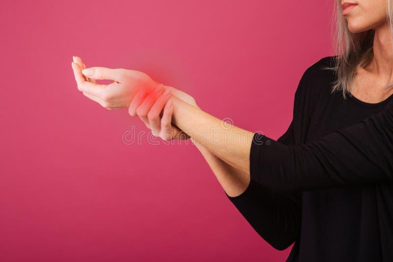 握她美丽的健康腕子健康在前方和按摩在痛苦区域的妇女 库存图片